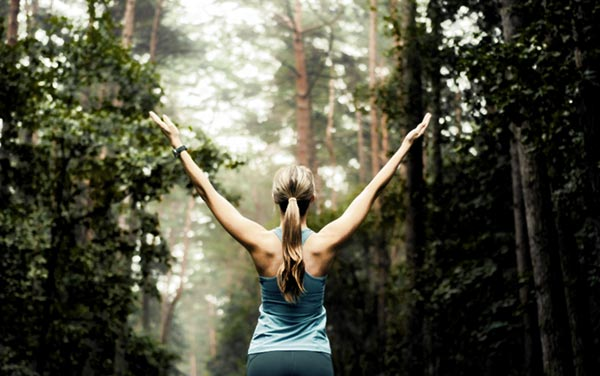 Runner in Woods with Hands Raised